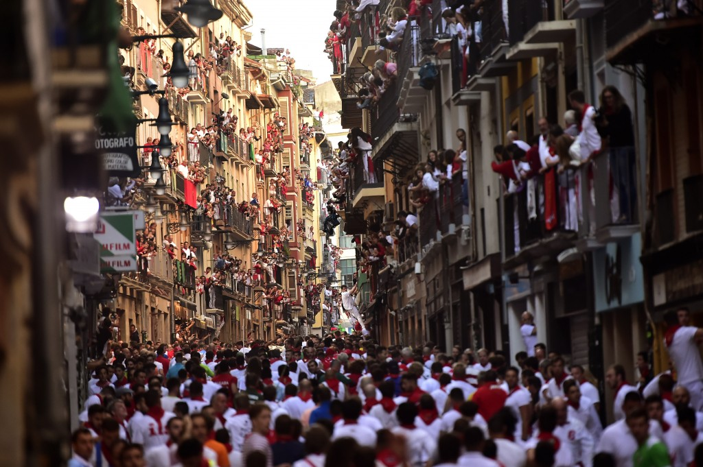 Revellers stand at the street ahead of the running of the bulls during the San Fermin Festival, in Pamplona, northern Spain, Thursday, July, 11, 2019....