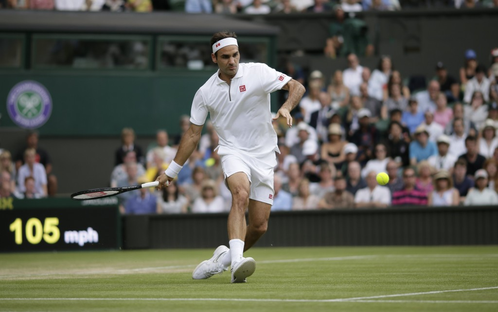 Switzerland's Roger Federer returns the ball to Japan's Kei Nishikori during a men's quarterfinal match on day nine of the Wimbledon Tennis Championsh...