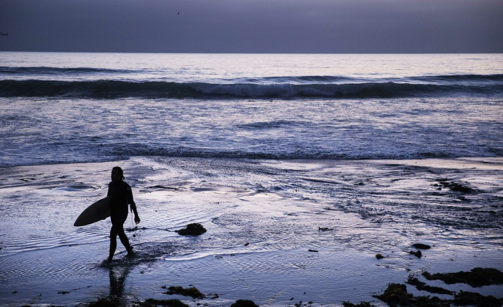 FILE - In this July 2, 2019, file photo a surfer walks out of the water after riding waves at dusk at Scripps Beach in San Diego. With hotel and airli...