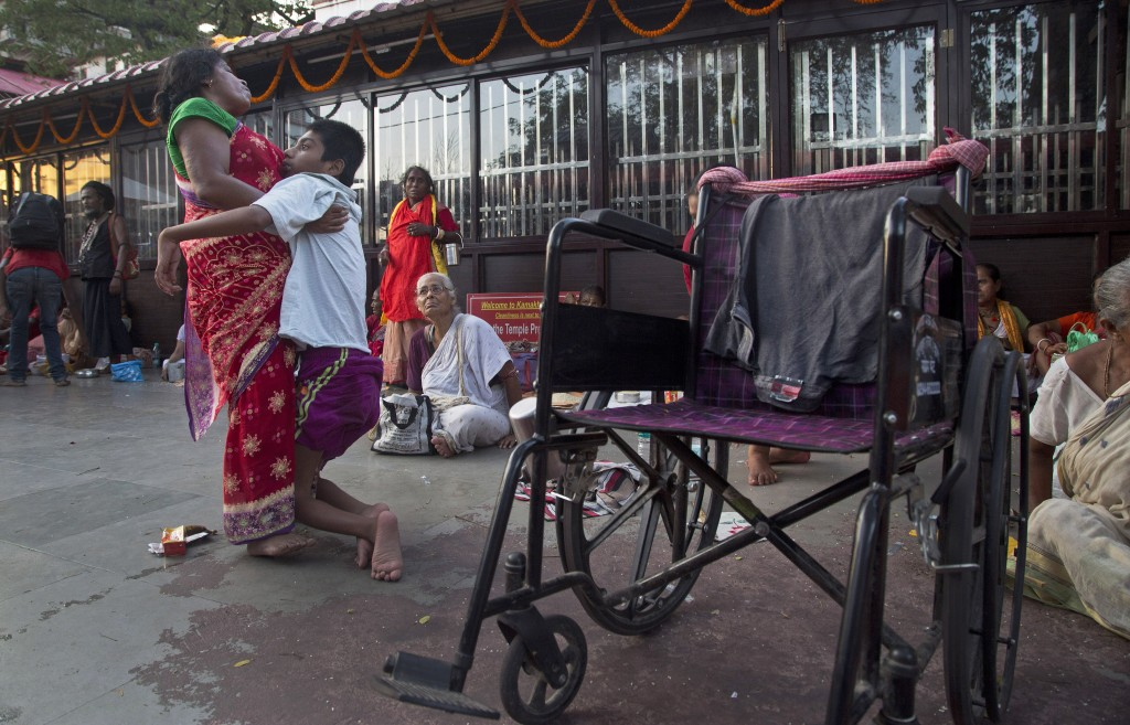 In this June 23, 2019 photo, Monika Deb Nath, 45, helps her son Gopal, 17, towards his wheelchair at the Kamakhya temple during the Ambubachi festival
