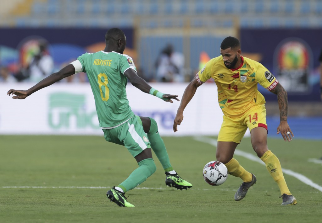 Senegal's Cheikhou Kouyate, left, and Benin's Cebio Soukou fight for the ball during the African Cup of Nations quarterfinal soccer match between Sene