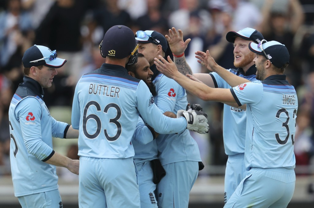 England's bowler Adil Rashid, middle, celebrates with teammates after dismissing Australia's Pat Cummins for 6 runs during the Cricket World Cup semi-