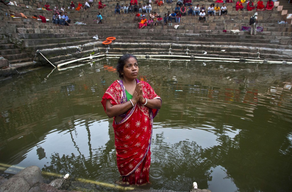 In this June 25, 2019 photo, Monika Deb Nath, 45, offers prayers before taking a dip in the temple pond at the Kamakhya temple during the Ambubachi fe
