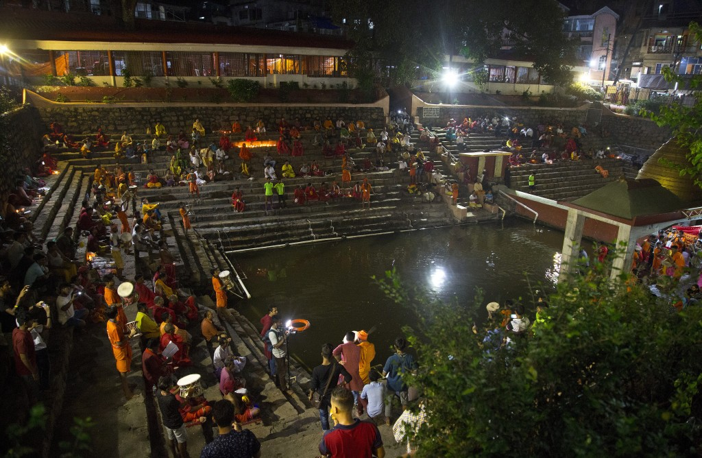 In this June 23, 2019 photo, devotees perform rituals by the holy pond at the Kamakhya temple during Ambubachi festival in Gauhati, India. The temple