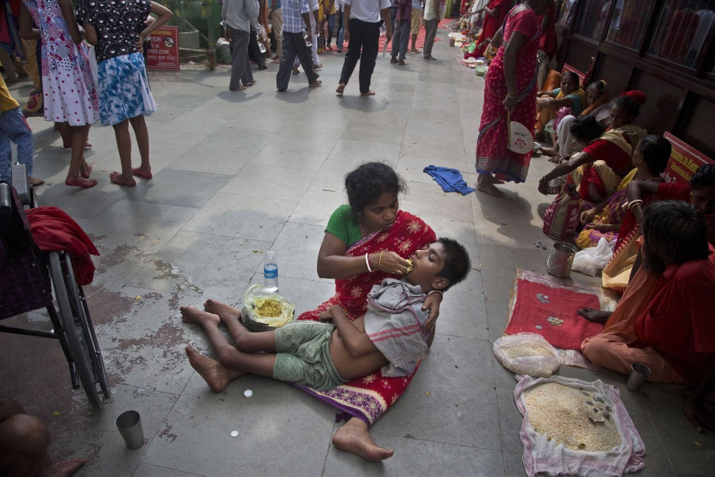 In this June 25, 2019 photo, Monika Deb Nath, 45, feeds her son Gopal, 17, at the Kamakhya temple during the Ambubachi festival in Gauhati, India. Mon