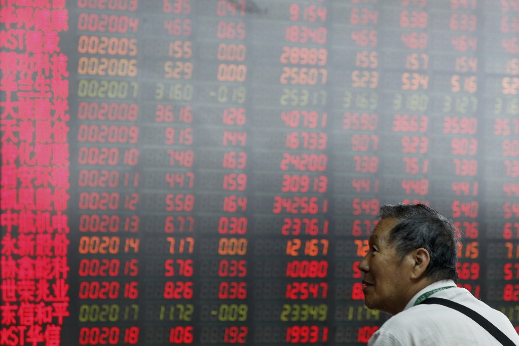A man monitors stock prices at a brokerage house i...