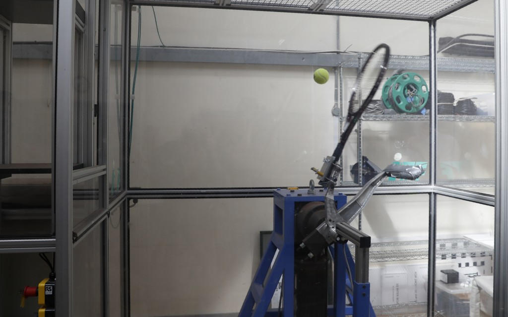 """In this photo taken Friday June, 28, 2019, a serve-simulating robot arm nicknamed """"Myo,"""" from the Greek word for """"muscle"""" is about to hit a ball dropp"""