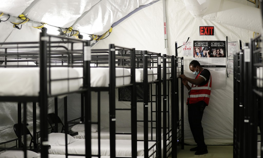 In this July 9, 2019, photo, a staff member works in the infirmary, a series of tents, at the U.S. government's newest holding center for migrant chil
