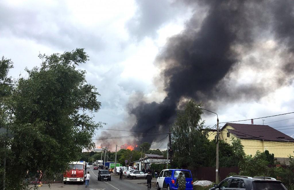 Black smoke rises over a power station, in Mytishc...