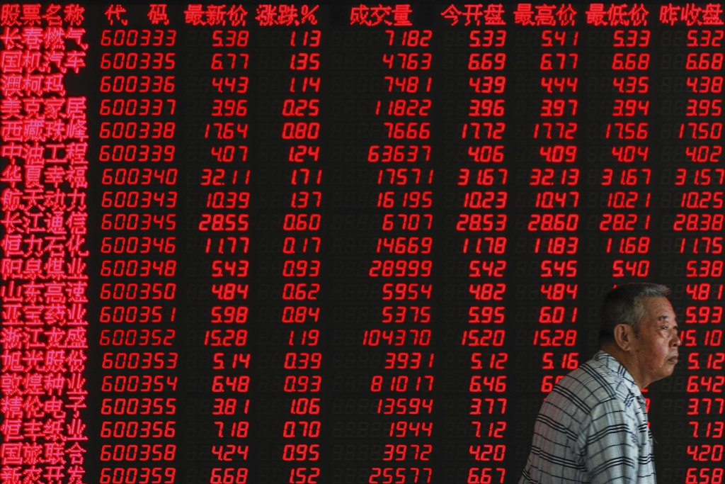 An investor walks by an electronic board displaying stock prices at a brokerage house in Beijing, Thursday, July 11, 2019. Shares rose Thursday in Asi