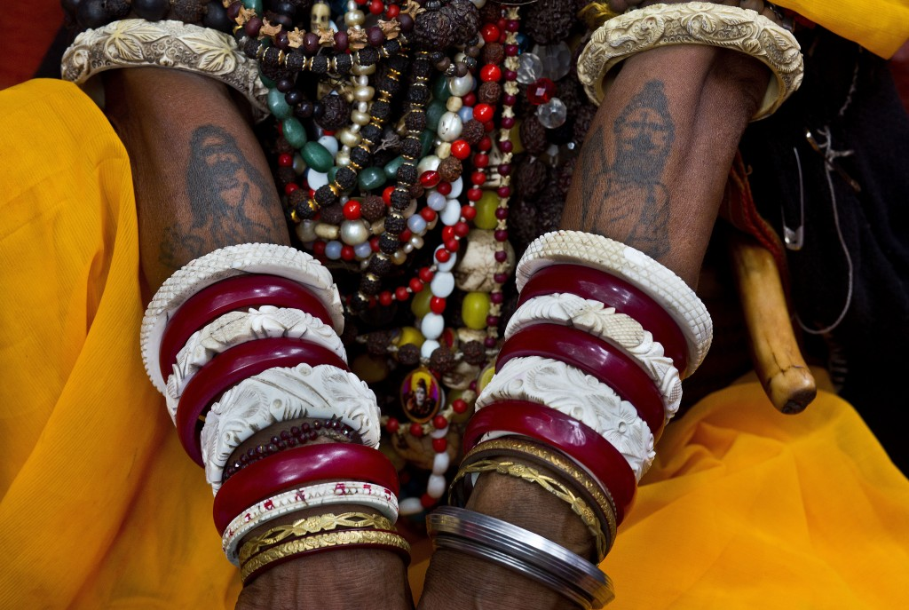 In this June 26, 2019 photo, a sadhvi, or Hindu holy woman, sits with her hands tattooed with images of Hindu god Shiva during Ambubachi festival at t