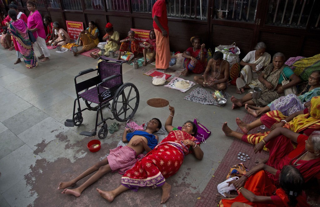 In this June 25, 2019 photo, Monika Deb Nath, 45, uses a hand fan and rests on the floor with her son Gopal, 17, at the Kamakhya temple during the Amb...