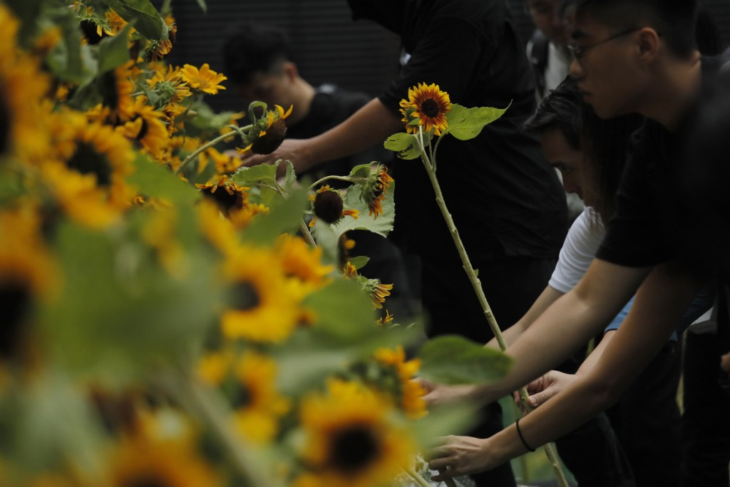 Attendees take part in a public memorial for Marco Leung, the 35-year-old man who fell to his death weeks ago after hanging a protest banner against a...