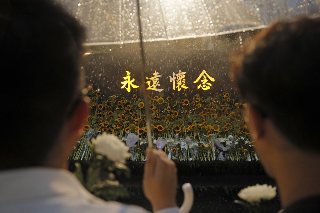 Attendees take part in a public memorial for Marco Leung, the 35-year-old man who fell to his death weeks ago after hanging a protest banner against a