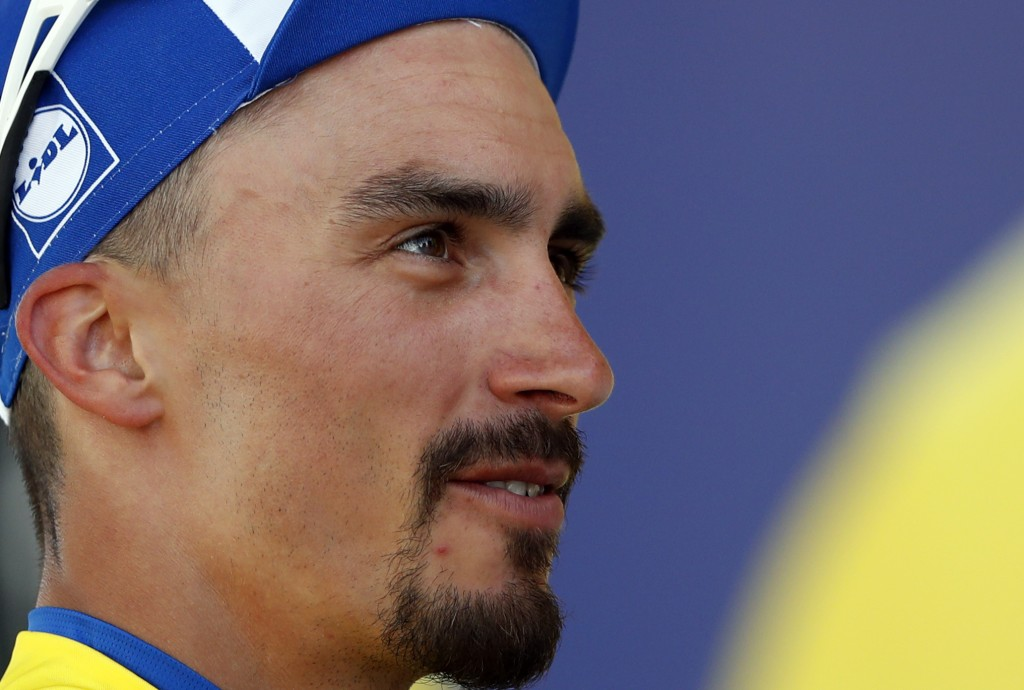 France's Julian Alaphilippe wearing the overall leader's yellow jersey stands on the podium after the fifth stage of the Tour de France cycling race o...