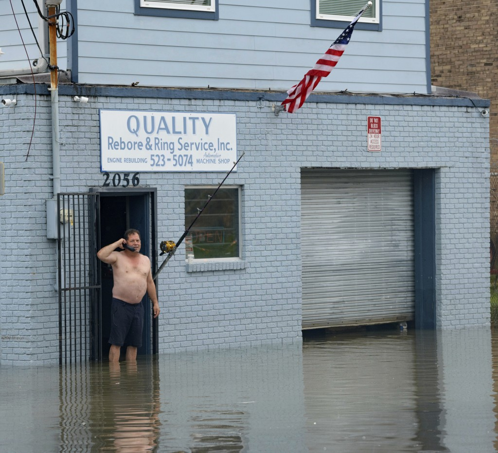 David Fox makes a call from his business on Poydras Street in New Orleans after flooding in New Orleans Wednesday, July 10, 2019. A storm swamped New