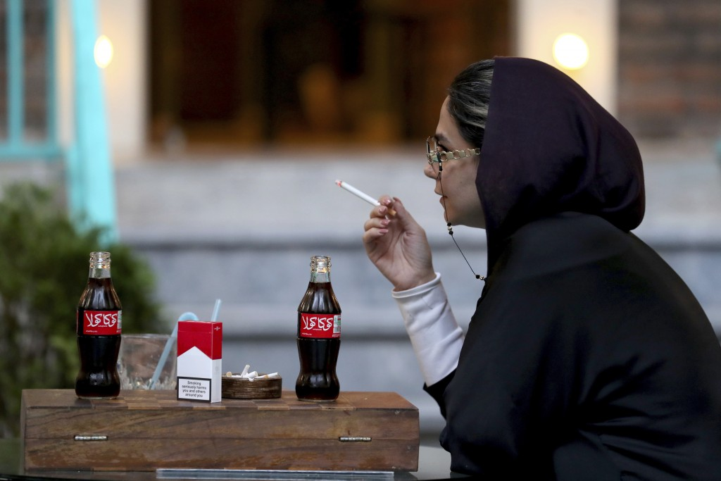 An Iranian smokes a Marlboro cigarette while two Coca-Cola stand on her table at a cafe in downtown Tehran, Iran, Wednesday, July 10, 2019. Whether at