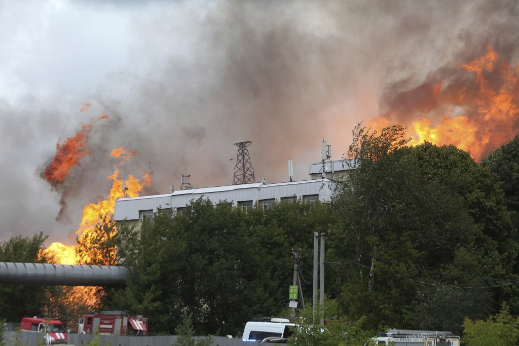 Black smoke and flames rise over a power station, ...