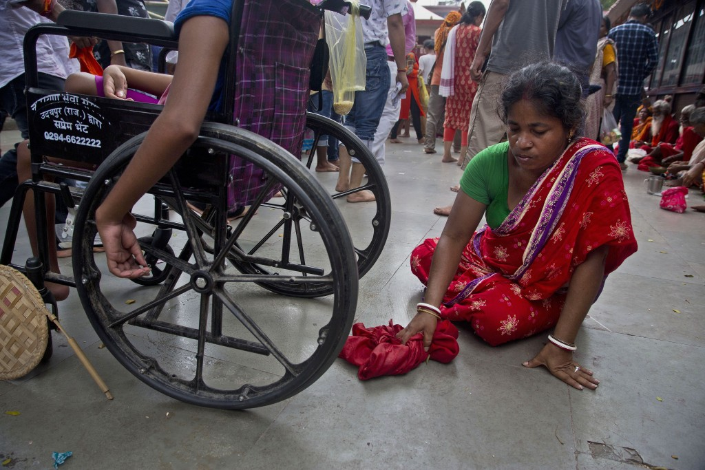 In this June 25, 2019 photo, Monika Deb Nath, 45, cleans the floor of urine excreted by her son Gopal, 17, at the Kamakhya temple during the Ambubachi
