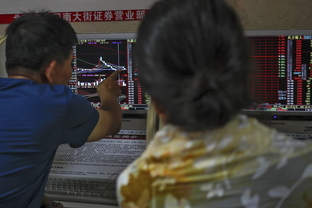 Chinese investors chat at each other as they monit...