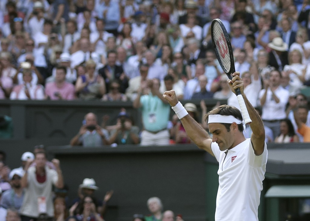 Switzerland's Roger Federer celebrates defeating Japan's Kei Nishikori during a men's quarterfinal match on day nine of the Wimbledon Tennis Champions