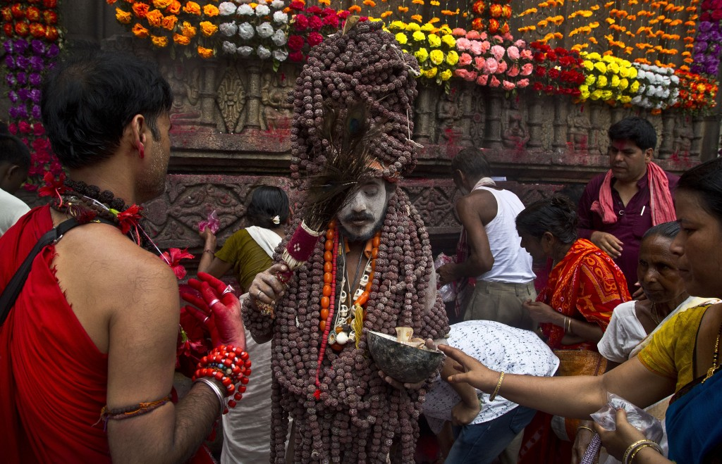 In this June 25, 2019 photo, a Sadhu, or Hindu holy man, blesses devotees during Ambubachi festival at Kamakhya temple in Gauhati, India. The temple i...