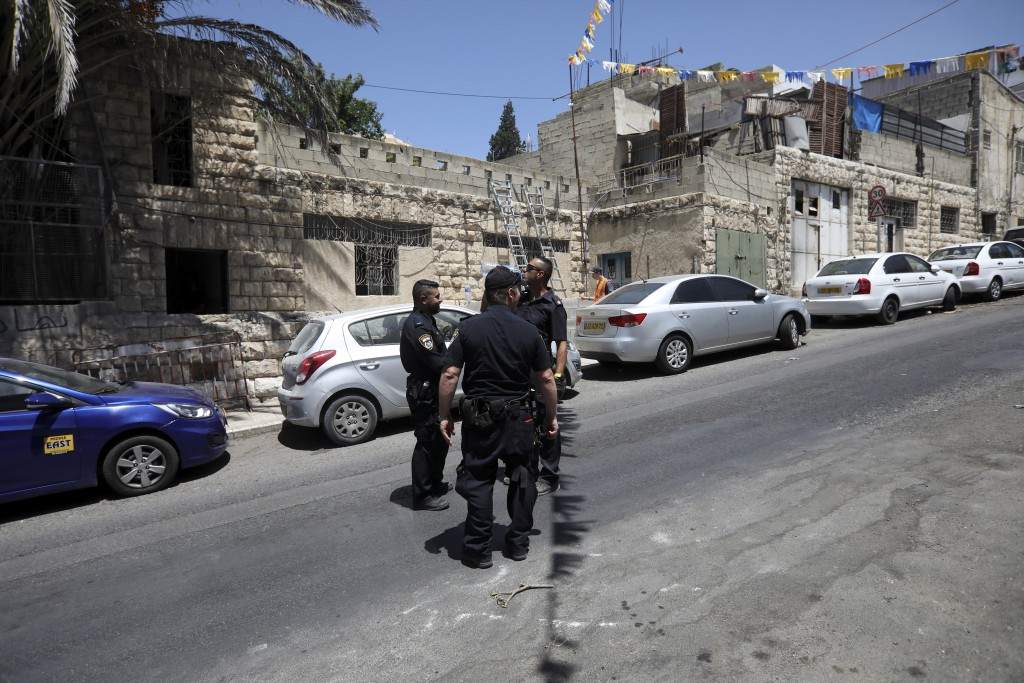 Israeli police stand in front of a house after a P...