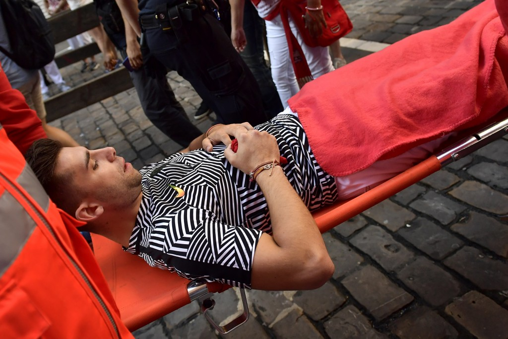 A reveller is taken on a stretcher after being injured during the running of the bulls at the San Fermin Festival, in Pamplona, northern Spain, Thursd...