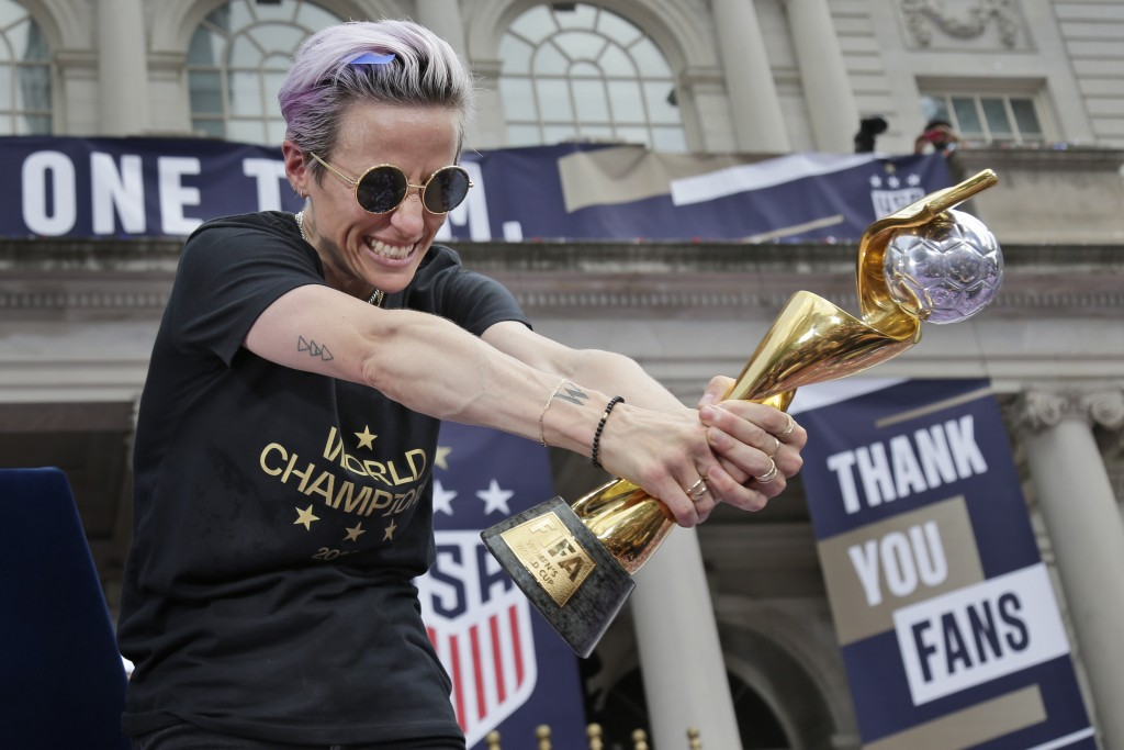U.S. women's soccer player Megan Rapinoe celebrates with the FIFA Women's World Cup trophy at City Hall after a ticker tape parade, Wednesday, July 10...