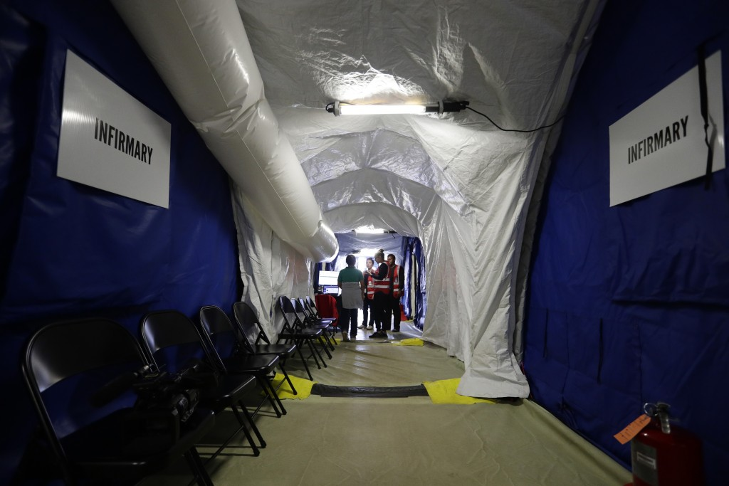 In this July 9, 2019, photo, an immigrant is attended to in the infirmary at the U.S. government's newest holding center for migrant children in Carri...