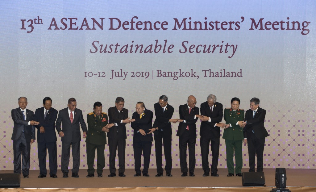 ASEAN defense ministers prepare to join hands for a group photo ahead of the ASEAN Defense Ministers' Meeting Thursday, July 11, 2019, in Bangkok, Tha...