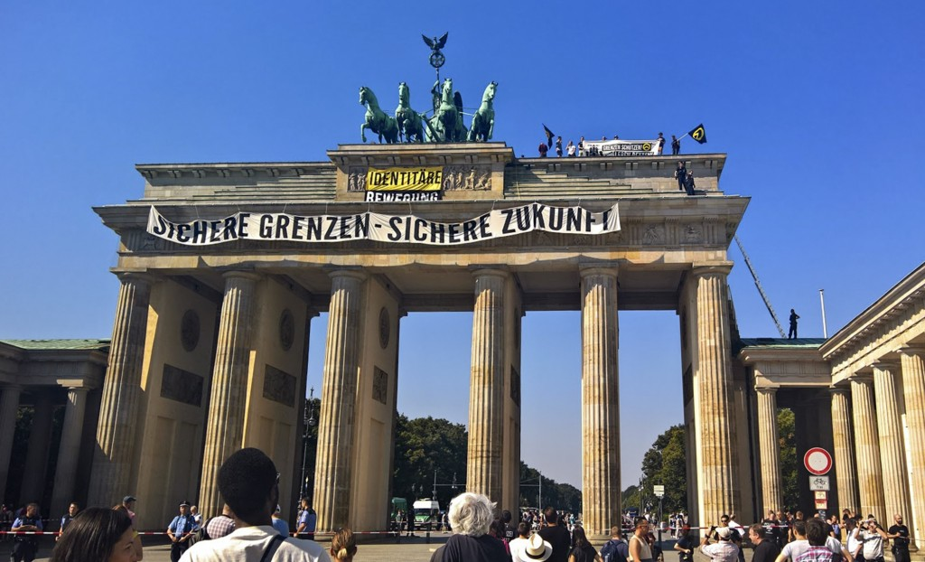 FILE - In this Aug. 27, 2016 file photo, activists of the Identitarian Movement protest on the Brandenburg Gate in Berlin, Germany, with a banner read