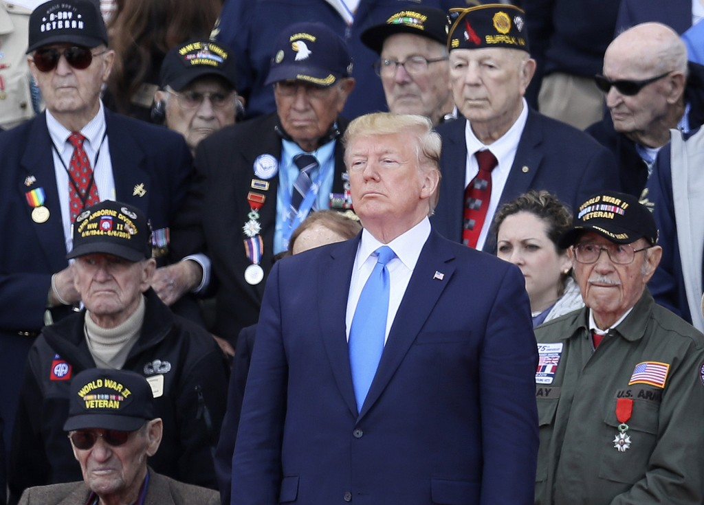 FILE - In this June 6, 2019 file photo, President Donald Trump stands with World War II veterans during a ceremony to mark the 75th anniversary of D-D
