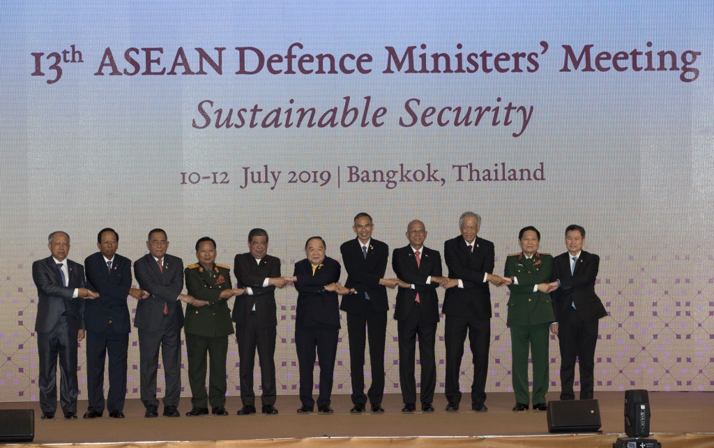 ASEAN defense ministers shake hands for a group photo ahead of the ASEAN Defense Ministers' Meeting Thursday, July 11, 2019, in Bangkok, Thailand. The...