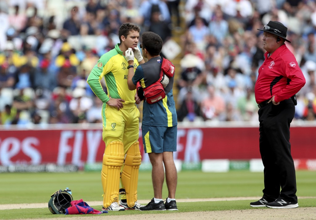 Australia's Alex Carey, left, is attended by a medic after he was hit off the bowling of England's Jofra Archer during the Cricket World Cup semi-fina...
