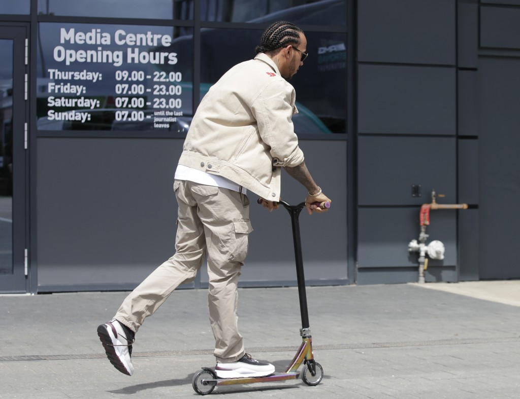 Mercedes driver Lewis Hamilton of Britain rides a scooter in the paddock of the Silverstone racetrack, in Silverstone, England, Thursday, July 11, 201