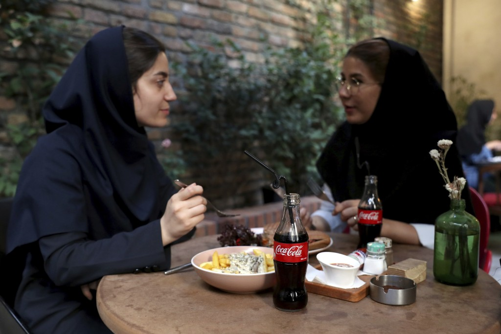 Two Iranians enjoy their time while two Coca-Cola stand on their table at a cafe in downtown Tehran, Iran, Wednesday, July 10, 2019. Whether at upscal
