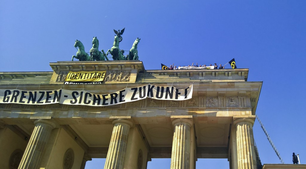 Activists of the Identitarian Movement protest on the Brandenburg Gate with a banner reading 'secure borders - secure fututre'Saturday, Aug. 27, 2016.