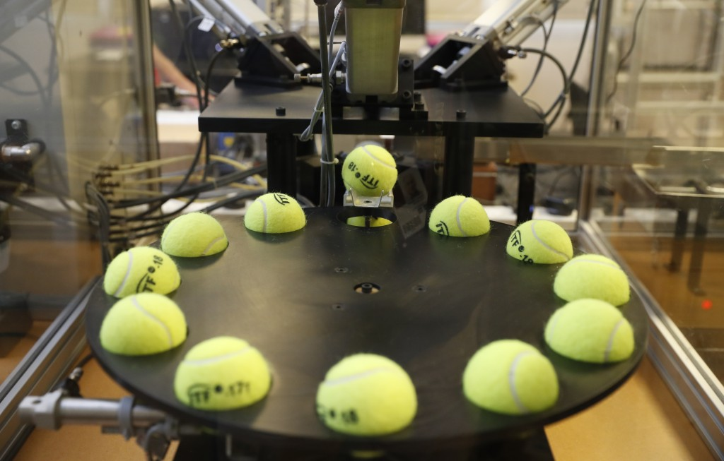 In this photo taken Friday June, 28, 2019, a tennis balls are lined up to squashed by pistons as they are tested by the International Tennis Federatio