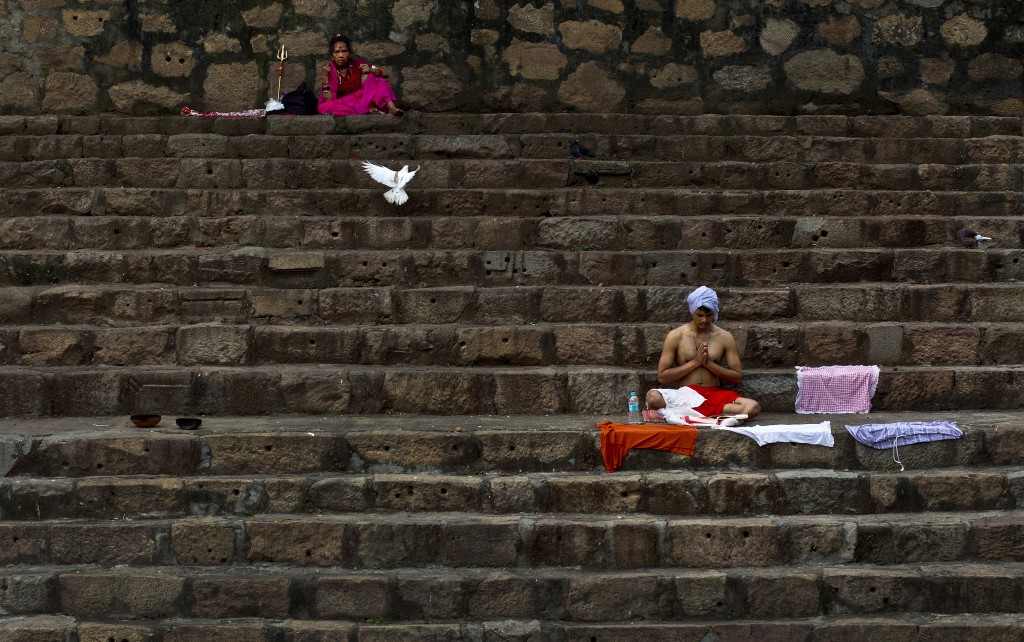 In this June 22, 2019 photo, devotees perform rituals sitting on steps of the Kamakhya temple during the Ambubachi festival in Gauhati, India. The tem...