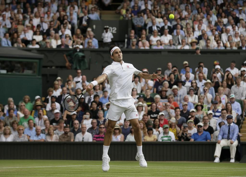 Switzerland's Roger Federer returns the ball to Ja...