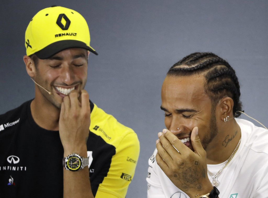 Mercedes driver Lewis Hamilton of Britain laughs with Renault driver Daniel Ricciardo of Australia during a news conference at the Silverstone racetra