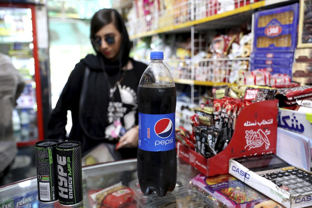 An Iranian Customer buys a Pepsi in a grocery store in downtown Tehran, Iran, Wednesday, July 10, 2019. Whether at upscale restaurants or corner store