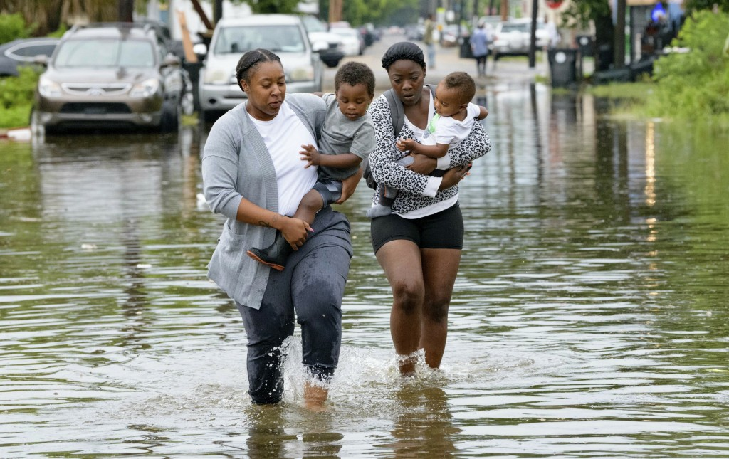 Jalana Furlough carries her son Drew Furlough as Terrian Jones carries Chance Furlough in New Orleans after flooding Wednesday, July 10, 2019.  (AP Ph...