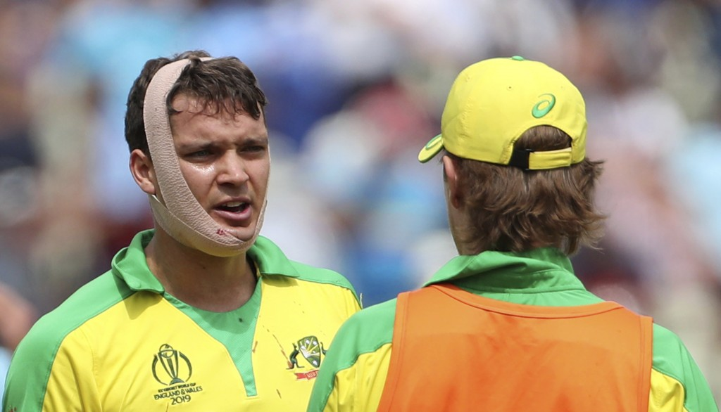 Australia's Alex Carey, left, talks to teammate Adam Zampa during a drinks break after he was hit off the bowling of England's Jofra Archer during the...
