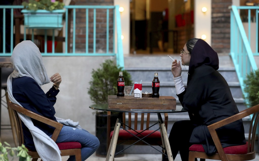 An Iranian smokes a Marlboro cigarette while two Coca-Cola stand on her table at a cafe in downtown Tehran, Iran, Wednesday, July 10, 2019. Whether at...