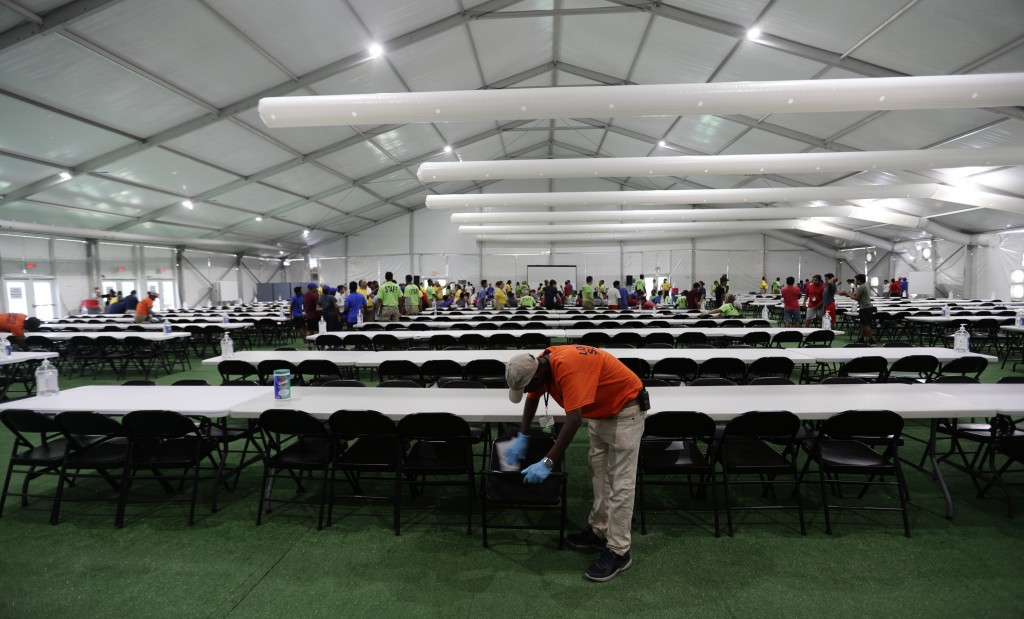 In this July 9, 2019, photo, a staff member cleans in a dinning hall at the U.S. government's newest holding center for migrant children in Carrizo Sp...