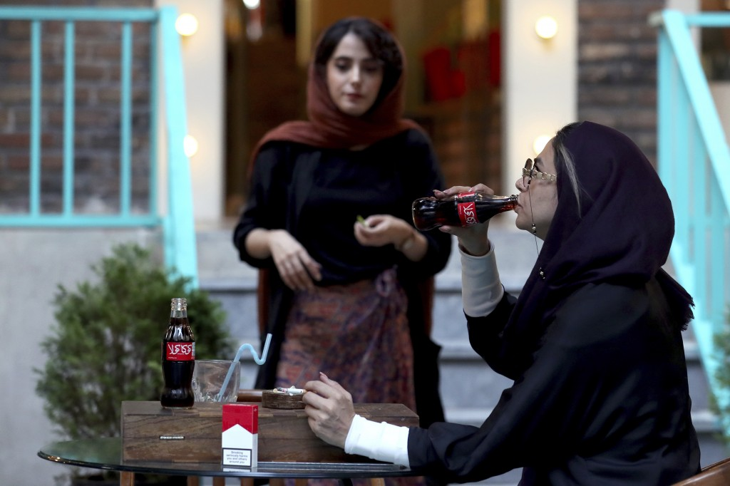An Iranian drinks a Coca-Cola and smokes a Marlboro cigarette at a cafe in downtown Tehran, Iran, Wednesday, July 10, 2019. Whether at upscale restaur