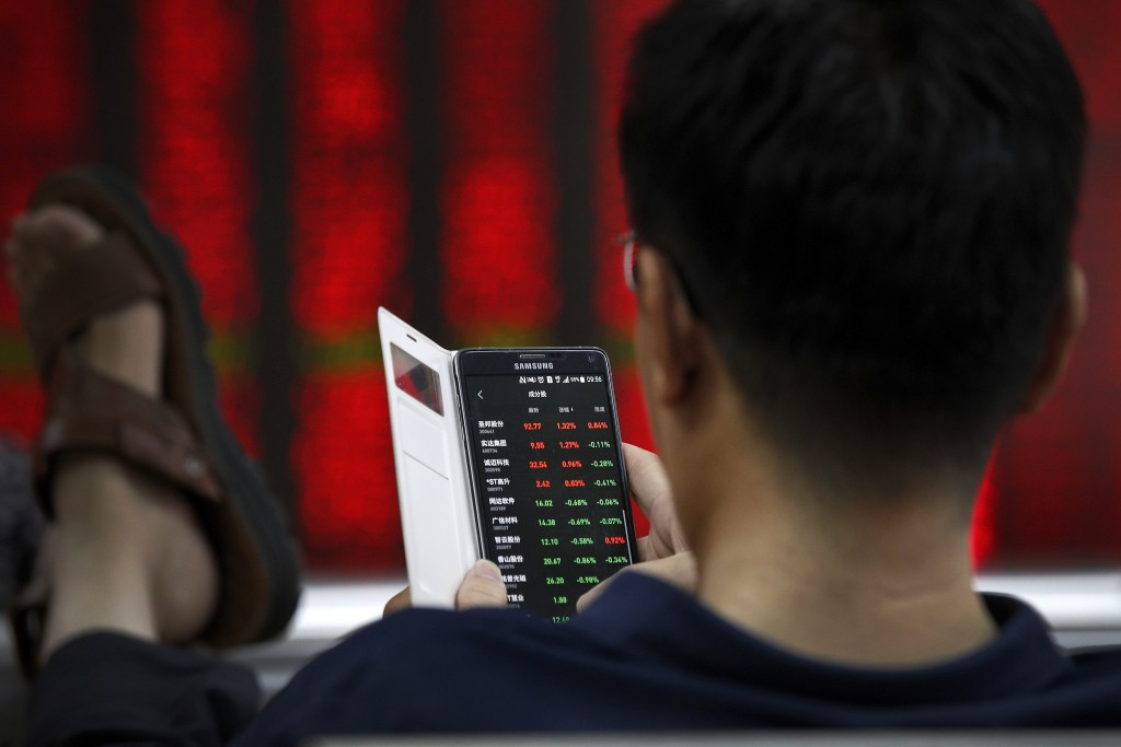 A man checks stock prices through his smartphone at a brokerage house in Beijing, Thursday, July 11, 2019. Shares rose Thursday in Asia, tracking gain