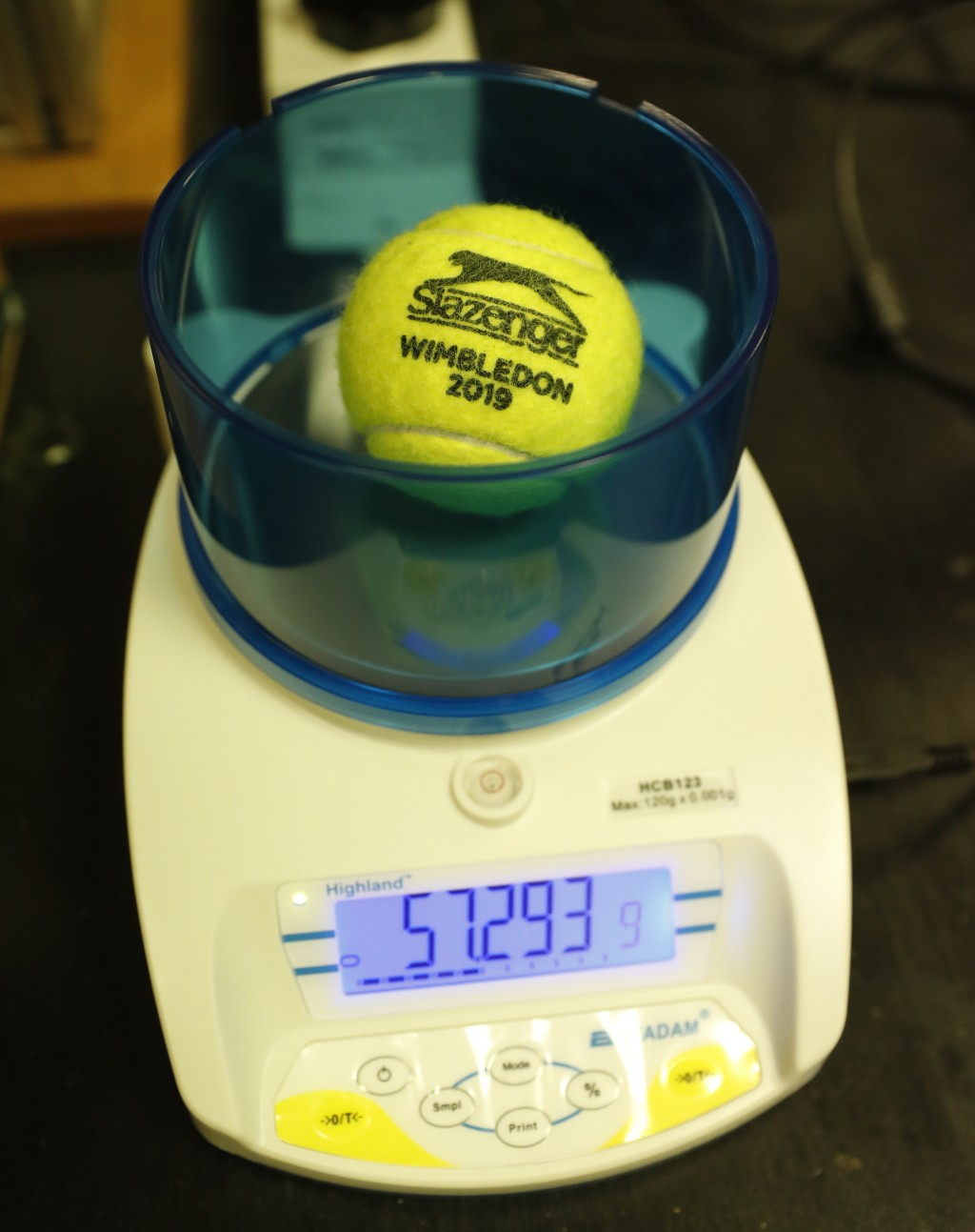 In this photo taken Friday June, 28, 2019, a Wimbledon 2019 tennis ball is weighed at the International Tennis Federation (ITF) lab in Roehampton, nea...